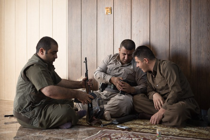 29/09/2015. Chamchamal, Iraq. Hardi (L), Sarwar (C) and Zana, all volunteer peshmerga fighters, reload ammunition ahead of a peshmerga offensive at a comrade's house in Chamchamal, Iraq.  Supported by coalition airstrikes around 3500 peshmerga of the Patriotic Union of Kurdistan (PUK) and the Kurdistan Democratic Party (KDP) engaged in a large offensive to push Islamic State militants out of villages to the west of Kirkuk. During previous offensives ISIS fighters withdrew after sustained coalition air support, but this time in many places militants stayed and fought. The day would see the coalition conduct around 50 airstrikes helping the joint peshmerga force to advance to within a few kilometres of the ISIS stronghold of Hawija and re-take around 17 villages. Around 20 peshmerga lost their lives to improvised explosive devices left by the Islamic State, reports suggest that between 40 and 150 militants were killed.