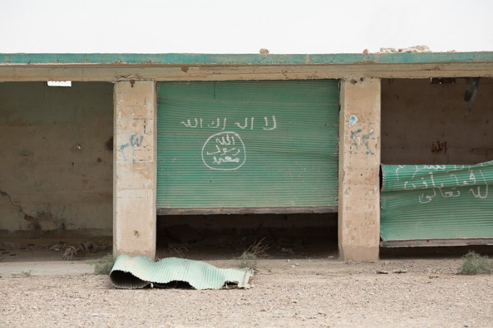 30/09/2015. Kirkuk, Iraq. Islamic State graffiti is seen on the doors of a garage in an area recently liberated by Kurdish peshmerga during a large offensive to push militants out of an area to the west of Kirkuk, Iraq. Supported by coalition airstrikes around 3500 peshmerga of the Patriotic Union of Kurdistan (PUK) and the Kurdistan Democratic Party (KDP) engaged in a large offensive to push Islamic State militants out of villages to the west of Kirkuk. During previous offensives ISIS fighters withdrew after sustained coalition air support, but this time in many places militants stayed and fought. The day would see the coalition conduct around 50 airstrikes helping the joint peshmerga force to advance to within a few kilometres of the ISIS stronghold of Hawija and re-take around 17 villages. Around 20 peshmerga lost their lives to improvised explosive devices left by the Islamic State, reports suggest that between 40 and 150 militants were killed.