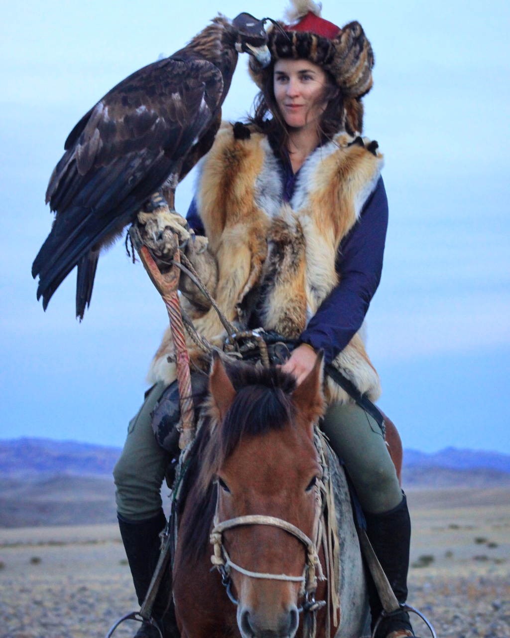 Chloe Phillips-Harris, 28, pictured holding an eagle and riding a horse in Mongolia, who was detained in Kazakhstan when officials refused to acknowledge her New Zealand passport, telling her it was a state of Australia. Supplied 30th November 2016