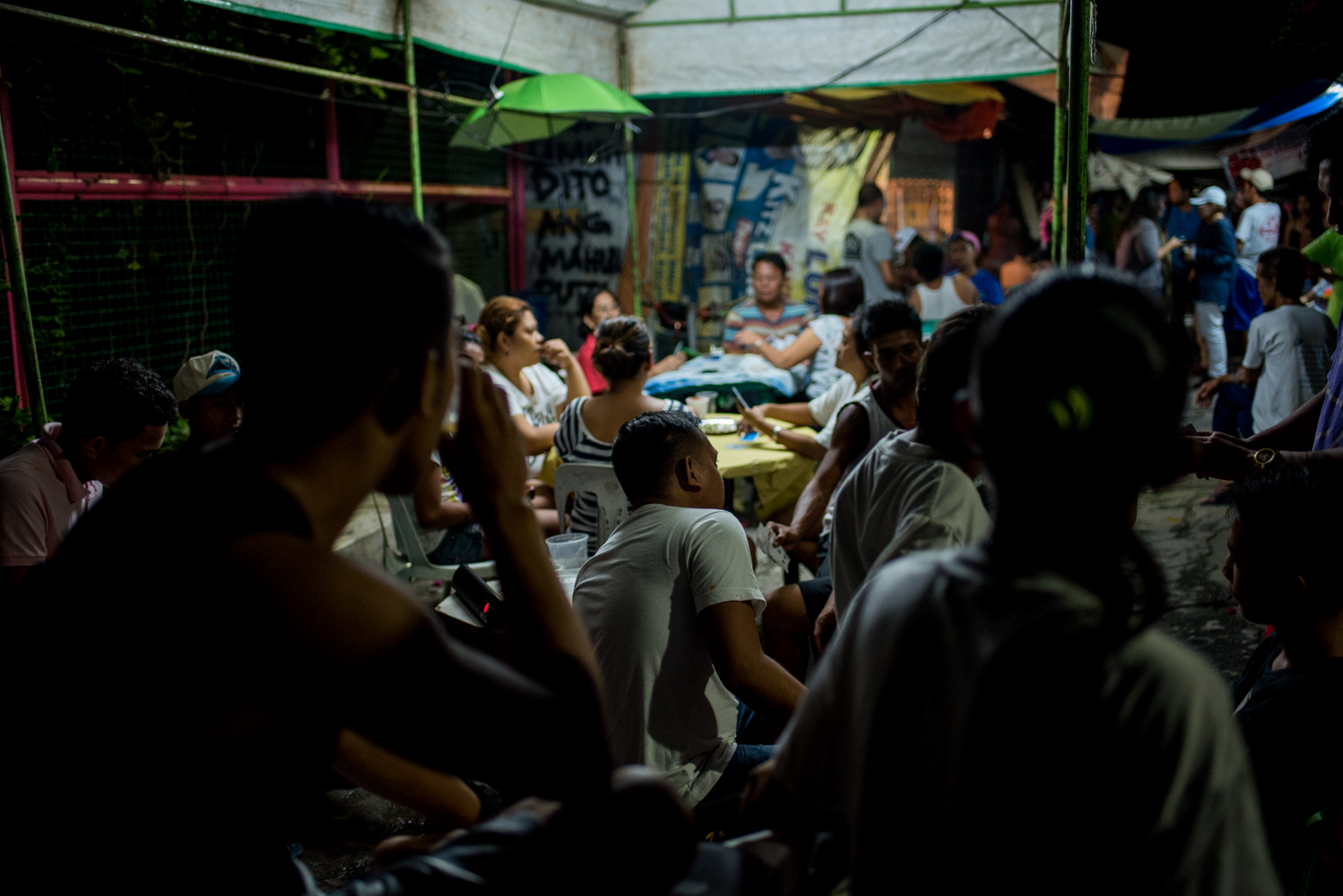 "Family and friends of Eric Sison play cards outside his wake to gather funds for his burial. Sison, a rickshaw driver, was killed as he was surrendering in a ""routine anti-criminality patrol"" by Pasay Police on August 23 in Tramo, Pasay City."
