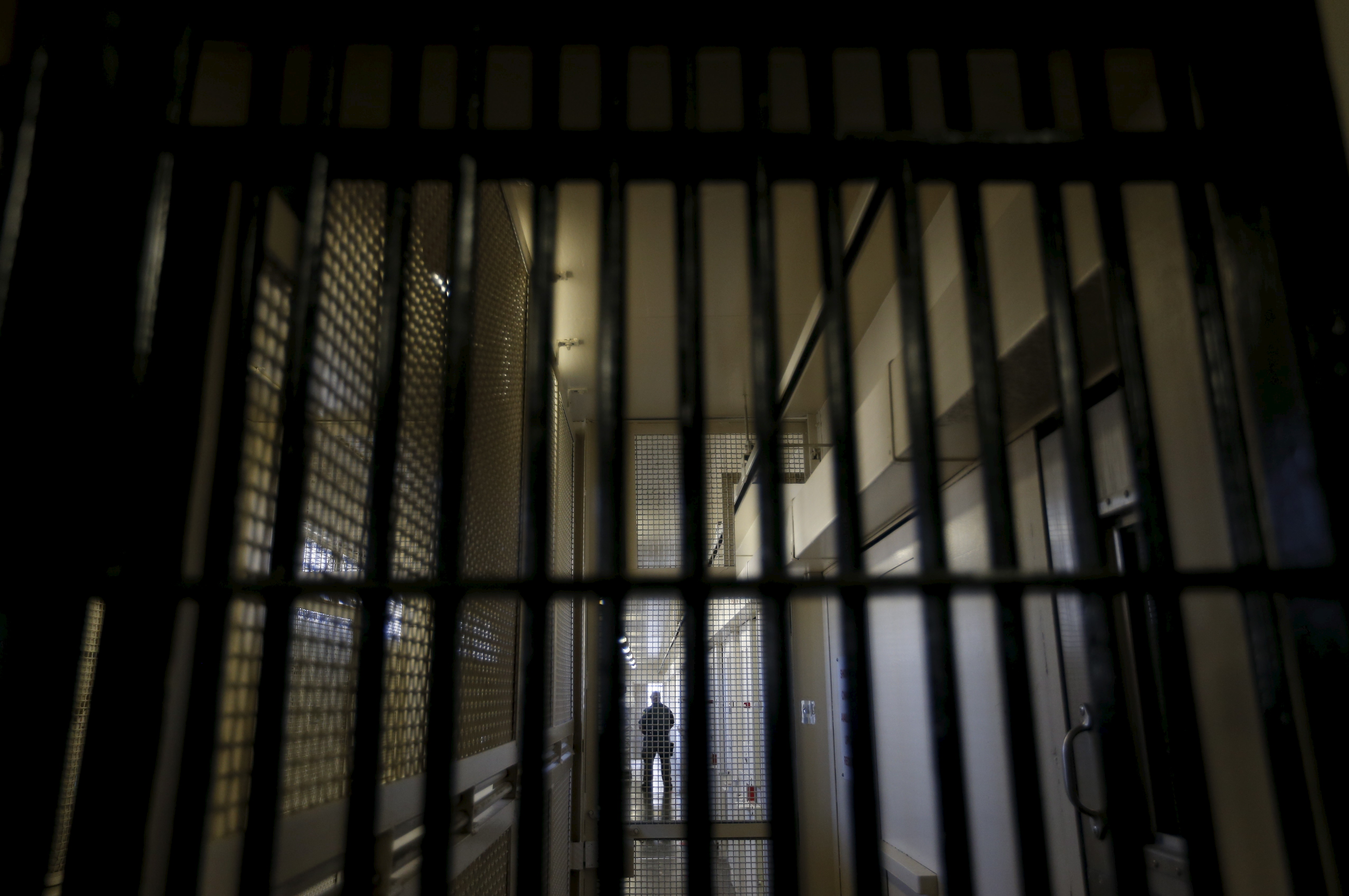 A guard stands behind bars at the Adjustment Center during a media tour of California's Death Row at San Quentin State Prison in San Quentin, California December 29, 2015. America's most populous state, which has not carried out an execution in a decade, begins 2016 at a pivotal juncture, as legal developments hasten the march toward resuming executions, while opponents seek to end the death penalty at the ballot box. To match Feature CALIFORNIA-DEATH-PENALTY/ Picture taken December 29, 2015. REUTERS/Stephen Lam - RTX21EDY