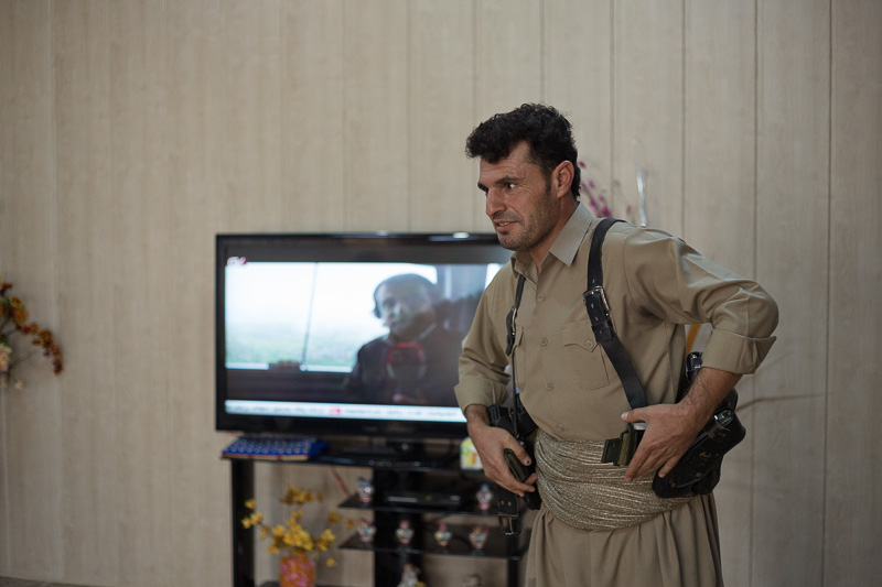 29/09/2015. Chamchamal, Iraq. Hadji Fazer, a volunteer peshmerga fighter, dons belt pouches containing ammunition in his home in Chamchamal Iraq as he and his group prepare to take part in a peshmerga offensive against ISIS held villages to the west of Kirkuk, Iraq. Supported by coalition airstrikes around 3500 peshmerga of the Patriotic Union of Kurdistan (PUK) and the Kurdistan Democratic Party (KDP) engaged in a large offensive to push Islamic State militants out of villages to the west of Kirkuk. During previous offensives ISIS fighters withdrew after sustained coalition air support, but this time in many places militants stayed and fought. The day would see the coalition conduct around 50 airstrikes helping the joint peshmerga force to advance to within a few kilometres of the ISIS stronghold of Hawija and re-take around 17 villages. Around 20 peshmerga lost their lives to improvised explosive devices left by the Islamic State, reports suggest that between 40 and 150 militants were killed.