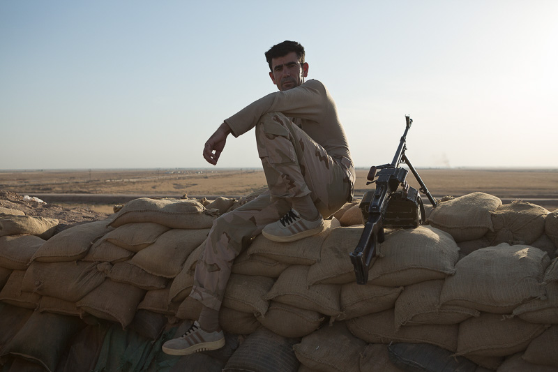 29/09/2015. Kirkuk, Iraq. A peshmerga sits on a sandbag wall next to a PKM machine gun at a front line west of Kirkuk, Iraq. Supported by coalition airstrikes around 3500 peshmerga of the Patriotic Union of Kurdistan (PUK) and the Kurdistan Democratic Party (KDP) engaged in a large offensive to push Islamic State militants out of villages to the west of Kirkuk. During previous offensives ISIS fighters withdrew after sustained coalition air support, but this time in many places militants stayed and fought. The day would see the coalition conduct around 50 airstrikes helping the joint peshmerga force to advance to within a few kilometres of the ISIS stronghold of Hawija and re-take around 17 villages. Around 20 peshmerga lost their lives to improvised explosive devices left by the Islamic State, reports suggest that between 40 and 150 militants were killed.