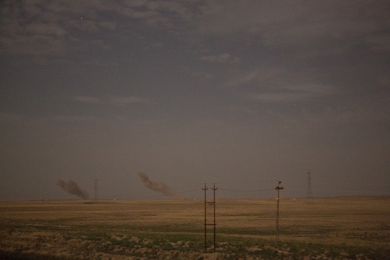 29/09/2015. Kirkuk, Iraq. Dust and smoke rises from the site of coalition airstrikes carries out on Islamic State positions in preparation for a large assault to capture several militant held villages to the west of Kirkuk, Iraq. Supported by coalition airstrikes around 3500 peshmerga of the Patriotic Union of Kurdistan (PUK) and the Kurdistan Democratic Party (KDP) engaged in a large offensive to push Islamic State militants out of villages to the west of Kirkuk. During previous offensives ISIS fighters withdrew after sustained coalition air support, but this time in many places militants stayed and fought. The day would see the coalition conduct around 50 airstrikes helping the joint peshmerga force to advance to within a few kilometres of the ISIS stronghold of Hawija and re-take around 17 villages. Around 20 peshmerga lost their lives to improvised explosive devices left by the Islamic State, reports suggest that between 40 and 150 militants were killed.
