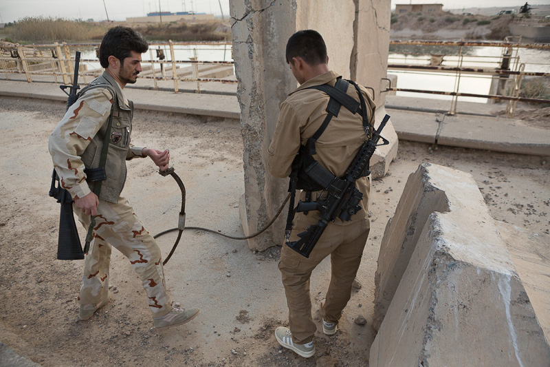 30/09/2015. Kirkuk, Iraq. Kurdish peshmerga fighters attach a steel strop to a concrete barrier, erected by ISIS militants to deny passage across a bridge, near the Iraqi town of Mansuriya during a large offensive by Kurdish security forces west of Kirkuk, Iraq. Supported by coalition airstrikes around 3500 peshmerga of the Patriotic Union of Kurdistan (PUK) and the Kurdistan Democratic Party (KDP) engaged in a large offensive to push Islamic State militants out of villages to the west of Kirkuk. During previous offensives ISIS fighters withdrew after sustained coalition air support, but this time in many places militants stayed and fought. The day would see the coalition conduct around 50 airstrikes helping the joint peshmerga force to advance to within a few kilometres of the ISIS stronghold of Hawija and re-take around 17 villages. Around 20 peshmerga lost their lives to improvised explosive devices left by the Islamic State, reports suggest that between 40 and 150 militants were killed.
