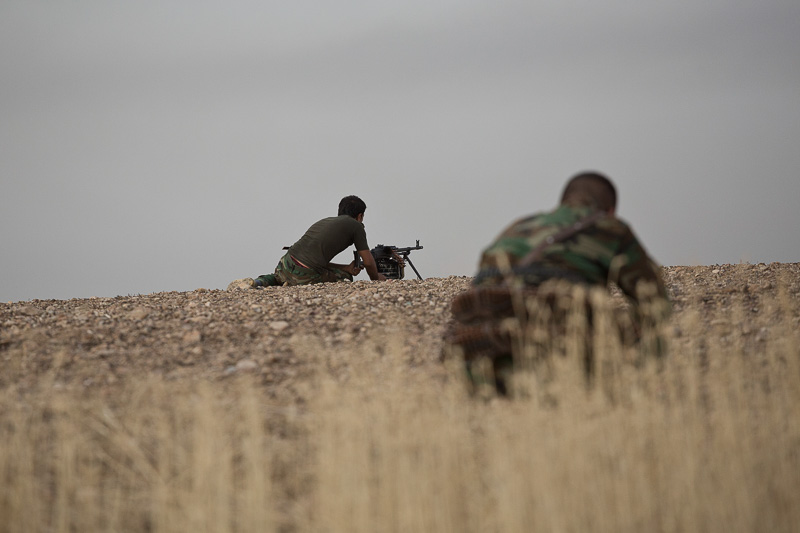 30/09/2015. Kirkuk, Iraq. Two peshmerga fighters hunker down as rounds from ISIS snipers and machine gunners fire at Kurds from the village of Mansuriya west of Kirkuk, Iraq. Supported by coalition airstrikes around 3500 peshmerga of the Patriotic Union of Kurdistan (PUK) and the Kurdistan Democratic Party (KDP) engaged in a large offensive to push Islamic State militants out of villages to the west of Kirkuk. During previous offensives ISIS fighters withdrew after sustained coalition air support, but this time in many places militants stayed and fought. The day would see the coalition conduct around 50 airstrikes helping the joint peshmerga force to advance to within a few kilometres of the ISIS stronghold of Hawija and re-take around 17 villages. Around 20 peshmerga lost their lives to improvised explosive devices left by the Islamic State, reports suggest that between 40 and 150 militants were killed.