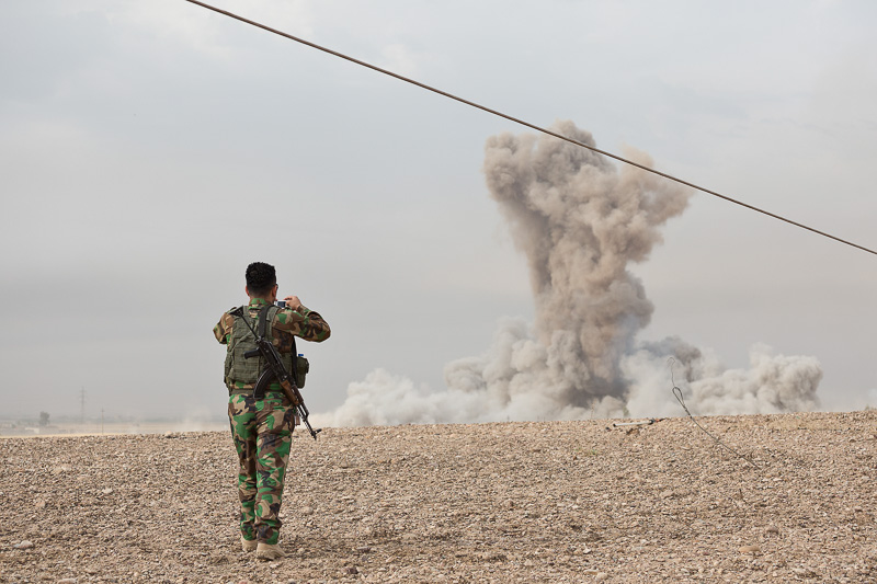 30/09/2015. Kirkuk, Iraq. A KDP peshmerga fighter takes a camera phone picture of a large plume of dust and smoke, one of two large bombs dropped on the village of Mansuriya by coalition aircraft to neutralise Islamic State positions that were pinning down peshmerga fighters during a Kurdish advance west of Kirkuk, Iraq. Supported by coalition airstrikes around 3500 peshmerga of the Patriotic Union of Kurdistan (PUK) and the Kurdistan Democratic Party (KDP) engaged in a large offensive to push Islamic State militants out of villages to the west of Kirkuk. During previous offensives ISIS fighters withdrew after sustained coalition air support, but this time in many places militants stayed and fought. The day would see the coalition conduct around 50 airstrikes helping the joint peshmerga force to advance to within a few kilometres of the ISIS stronghold of Hawija and re-take around 17 villages. Around 20 peshmerga lost their lives to improvised explosive devices left by the Islamic State, reports suggest that between 40 and 150 militants were killed.
