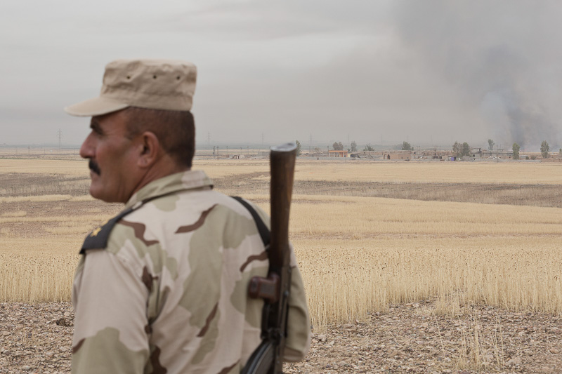30/09/2015. Kirkuk, Iraq. A Kurdish KDP peshmerga lieutenant colonel stands on a hill as fields burn beyond the village of Mansuriya west of Kirkuk, Iraq. Supported by coalition airstrikes around 3500 peshmerga of the Patriotic Union of Kurdistan (PUK) and the Kurdistan Democratic Party (KDP) engaged in a large offensive to push Islamic State militants out of villages to the west of Kirkuk. During previous offensives ISIS fighters withdrew after sustained coalition air support, but this time in many places militants stayed and fought. The day would see the coalition conduct around 50 airstrikes helping the joint peshmerga force to advance to within a few kilometres of the ISIS stronghold of Hawija and re-take around 17 villages. Around 20 peshmerga lost their lives to improvised explosive devices left by the Islamic State, reports suggest that between 40 and 150 militants were killed.