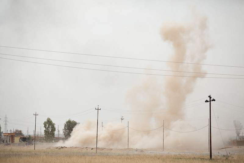 30/09/2015. Kirkuk, Iraq. A cloud of dust marks the spot where three peshmerga were fatally injured by an Islamic State improvised explosive device on the edge of Mansuriya village during an offensive to push militants out of several villages to the west of Kirkuk, Iraq. Supported by coalition airstrikes around 3500 peshmerga of the Patriotic Union of Kurdistan (PUK) and the Kurdistan Democratic Party (KDP) engaged in a large offensive to push Islamic State militants out of villages to the west of Kirkuk. During previous offensives ISIS fighters withdrew after sustained coalition air support, but this time in many places militants stayed and fought. The day would see the coalition conduct around 50 airstrikes helping the joint peshmerga force to advance to within a few kilometres of the ISIS stronghold of Hawija and re-take around 17 villages. Around 20 peshmerga lost their lives to improvised explosive devices left by the Islamic State, reports suggest that between 40 and 150 militants were killed.
