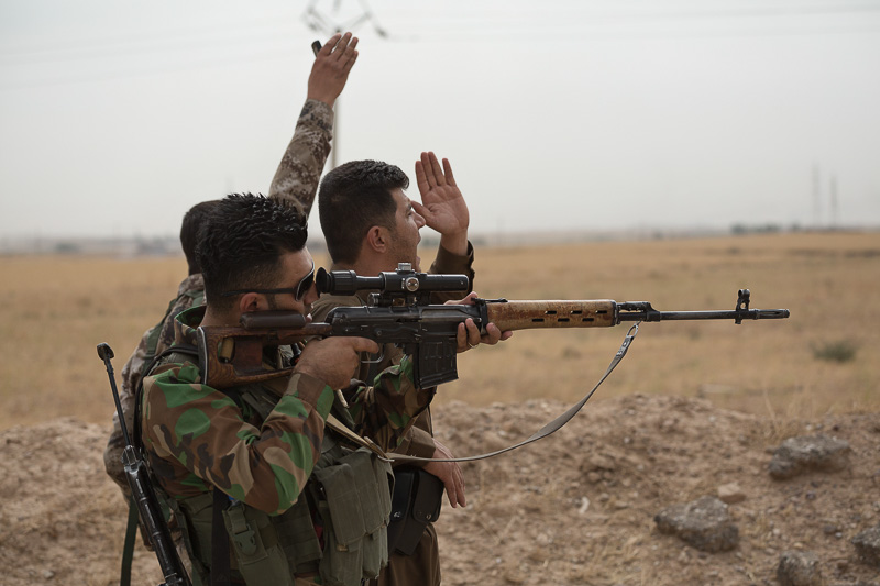 30/09/2015. Kirkuk, Iraq. Kurdish peshmerga and volunteer peshmerga wave and call to get the attention of comrades to bring up a stretcher and evacuate colleagues injured in an explosion caused by an Islamic State improvised explosive device. Supported by coalition airstrikes around 3500 peshmerga of the Patriotic Union of Kurdistan (PUK) and the Kurdistan Democratic Party (KDP) engaged in a large offensive to push Islamic State militants out of villages to the west of Kirkuk. During previous offensives ISIS fighters withdrew after sustained coalition air support, but this time in many places militants stayed and fought. The day would see the coalition conduct around 50 airstrikes helping the joint peshmerga force to advance to within a few kilometres of the ISIS stronghold of Hawija and re-take around 17 villages. Around 20 peshmerga lost their lives to improvised explosive devices left by the Islamic State, reports suggest that between 40 and 150 militants were killed.