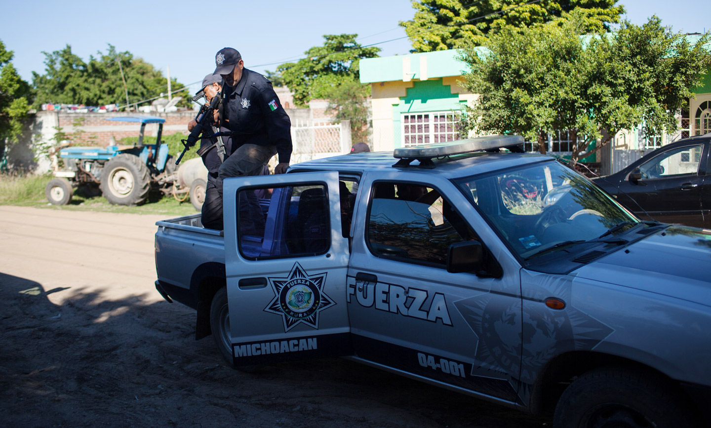 Members of the Fuerza Rural, more specifically a group lead by Hipolito Mora, get out of a truck in front of Mora's house, in La Ruana, Michoacán, Mexico, Tuesday, December 15, 2015. Hipolito Mora was one of the original founder of the autodefensa movement, which saw vigilantes spread across the state of Michoacán and drive out the cartel group the 'Knights of Templar'. Since the uprising began in 2013, other criminal groups have filled the space of the previous cartel and many look at the autodefensa movement as a failure. Mora has had many challenges over the last three years, including being sent to jail twice and having his son killed in a shootout Dec. 16, 2014 during a shootout with a rival group. (Brett Gundlock/Boreal Collective)