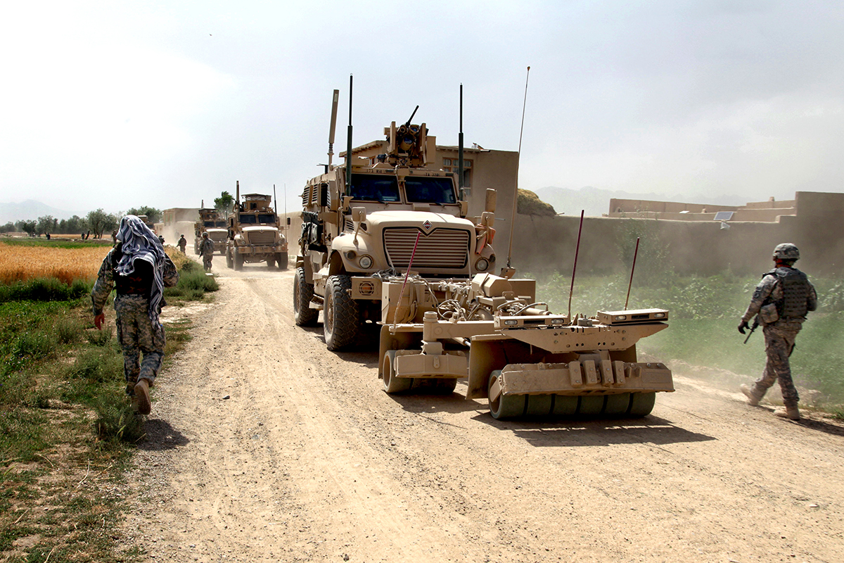 U.S. Army soldiers travel dismounted through the village of Kotub Kheyl as a convoy passes by June 24, Logar province, Afghanistan. Key leader engagements are conducted in this village to insure that there are no issue's and what can be done to prevent them.