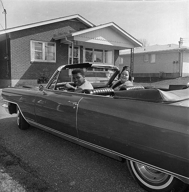 FILE - In this April 4, 1963 file photo, heavyweight boxer Cassius Clay is seen with his mother, Odessa Grady Clay, in a car outside their home in Louisville, Ky. The man who became the world's most recognizable athlete was a baby sitter, a jokester and a dreamer in the predominantly black West End neighborhood of Louisville where he grew up and forged lasting friendships while beginning his ascent toward greatness. Now, as the iconic boxer slowed by Parkinson's disease prepares to turn 70 next week, he's coming home for a birthday bash at the downtown cultural center and museum that bears his name. (AP Photo/H.B. Littell, File)