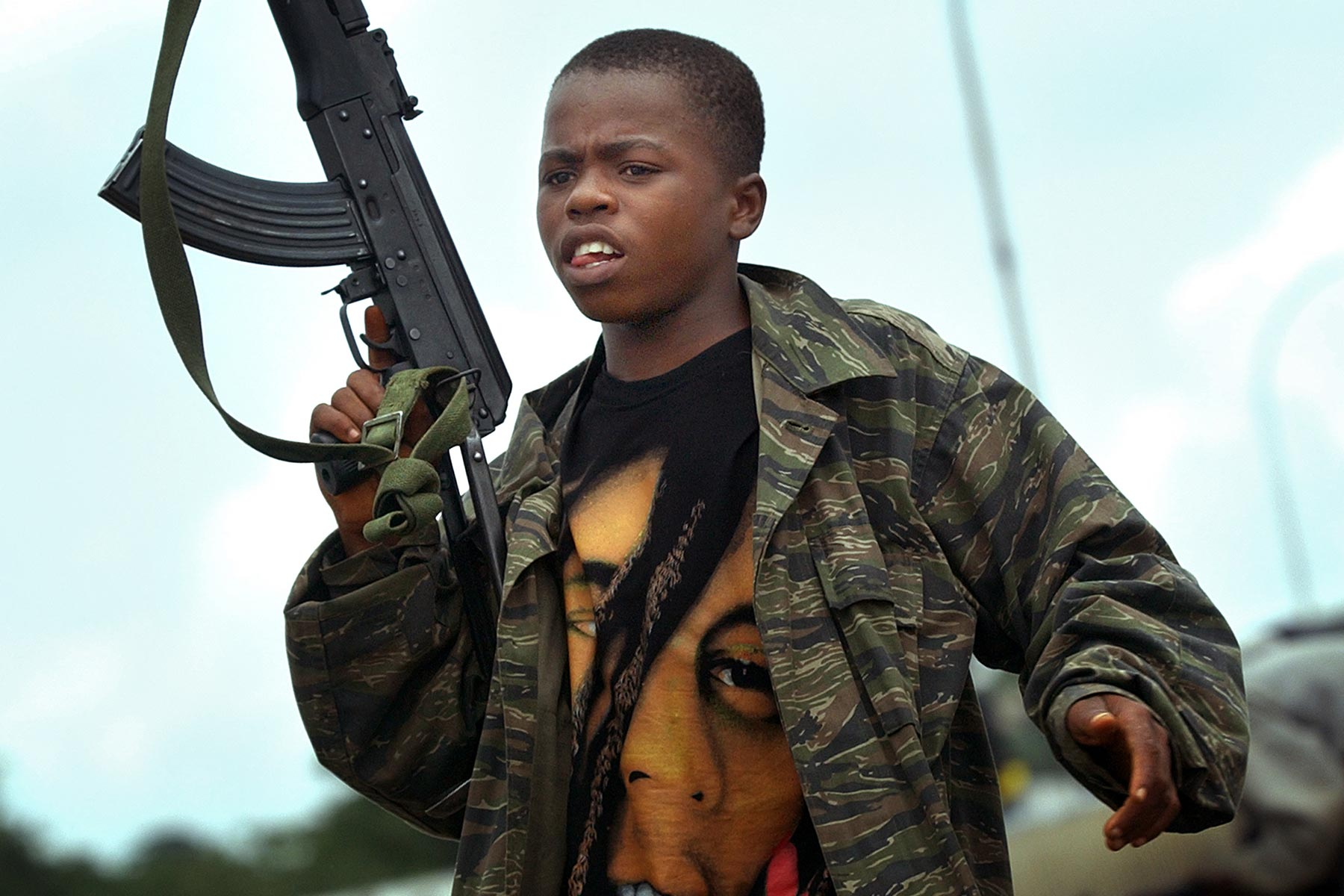 JULY 20, 2003 MONROVIA, LIBERIA Momo Dukoe,13, raises AK-47 rifles at the frontline in Monrovia, Liberia on July 20, 2003 as fighting between President Charles Taylor's troops and the rebel intensifies. Momo, who was forcefully recruited to the government militia, has been fighting since he was 11 years old. Photo by Kuni Takahashi