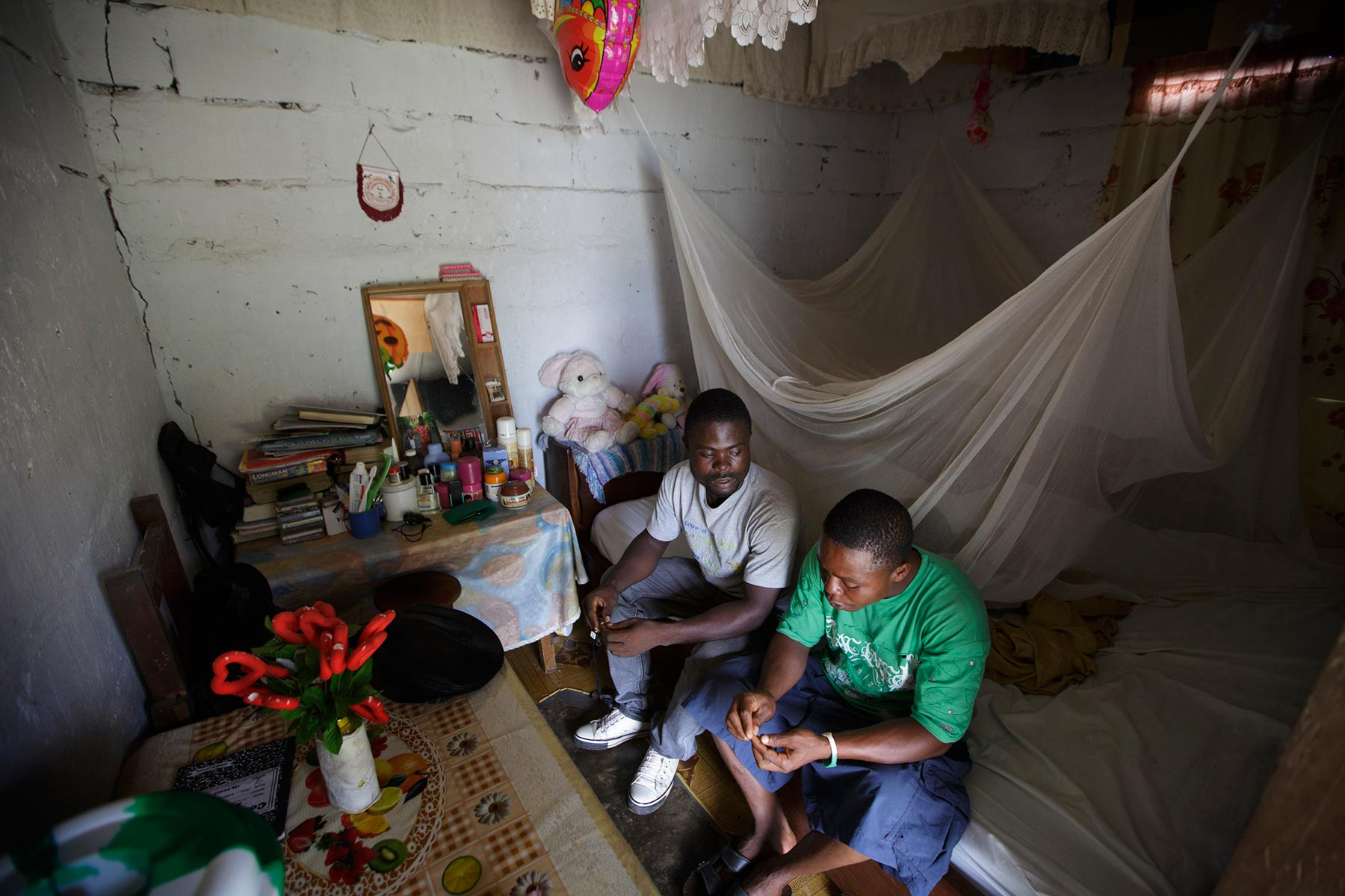 JUNE 3, 2015 MONROVIA, LIBERIA Former child soldier Momo Dukoe, 25, talks with one of his brother Daniel at Daniels room in Monrovia, Liberia on May 29, 2015. Momo, who was forcefully recruited to the government militia in his village in Lofa, northern Liberia when he was 11 years old, has fought for several years during the country's civil war which ended in Aug 2003. Photo by Kuni Takahashi