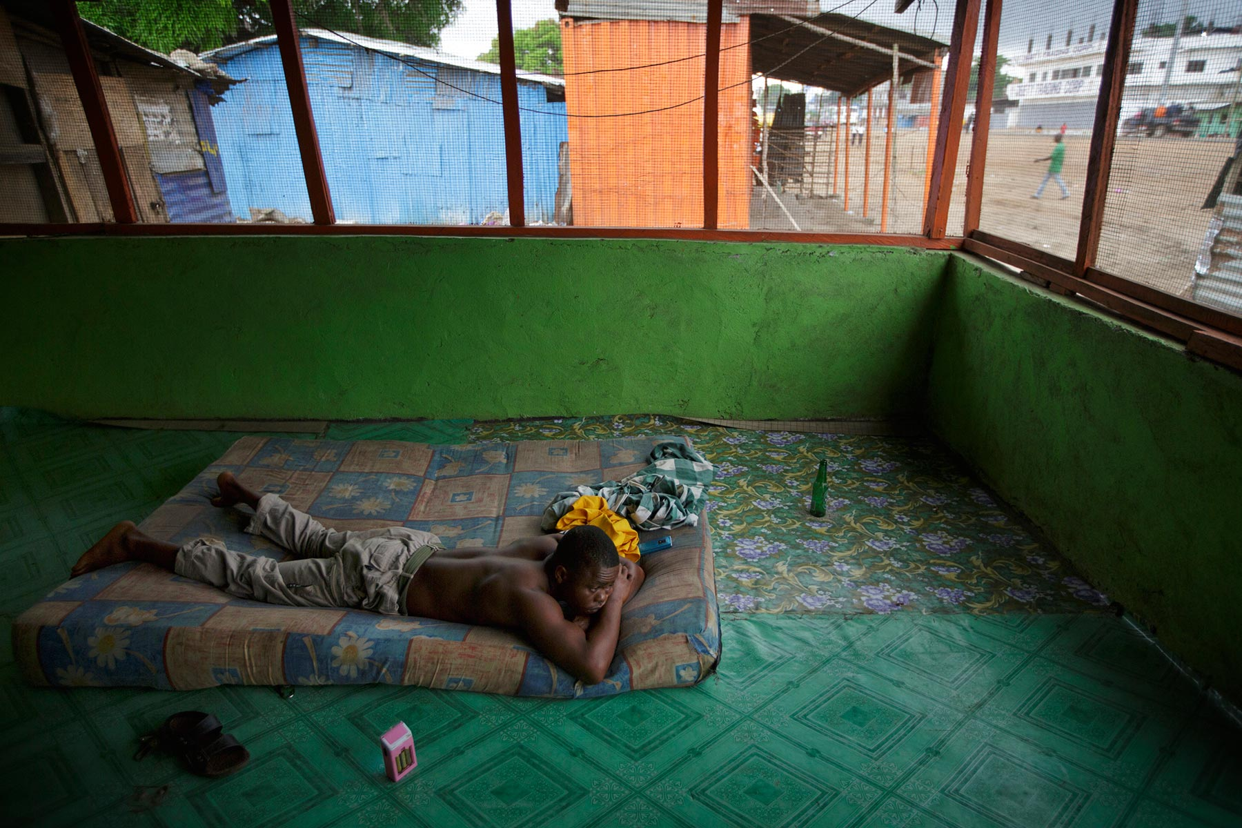 MAY 26, 2015 MONROVIA, LIBERIA Former child soldier Momo Dukoe, 25, lays down on mattress in early morning at the floor of restaurant where he sleeps during the night in Monrovia, Liberia on May 26, 2015. Momo, who was forcefully recruited to the government militia in his village in Lofa, northern Liberia when he was 11 years old, has fought for several years during the country's civil war which ended in Aug 2003. Photo by Kuni Takahashi