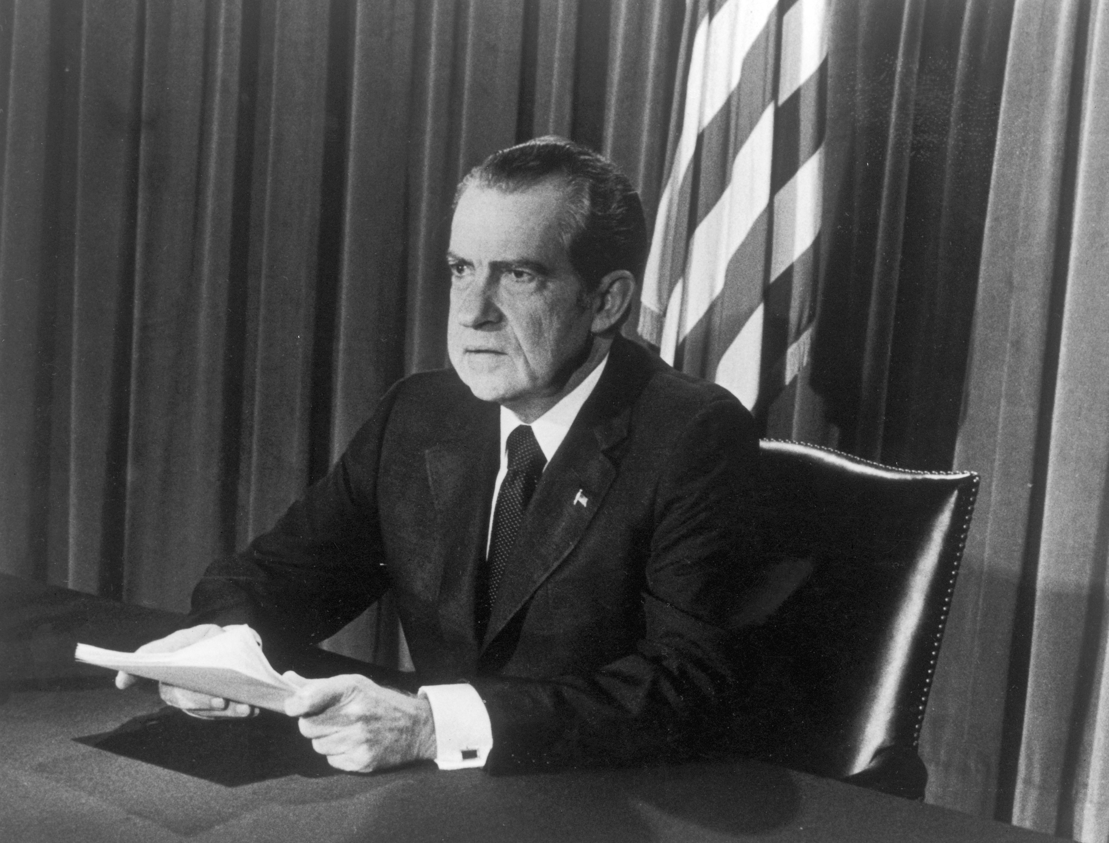 U.S. President Richard M. Nixon sits at a desk, holding papers, as he announces his resignation on television, Washington, D.C. (Photo by Hulton Archive/Getty Images)
