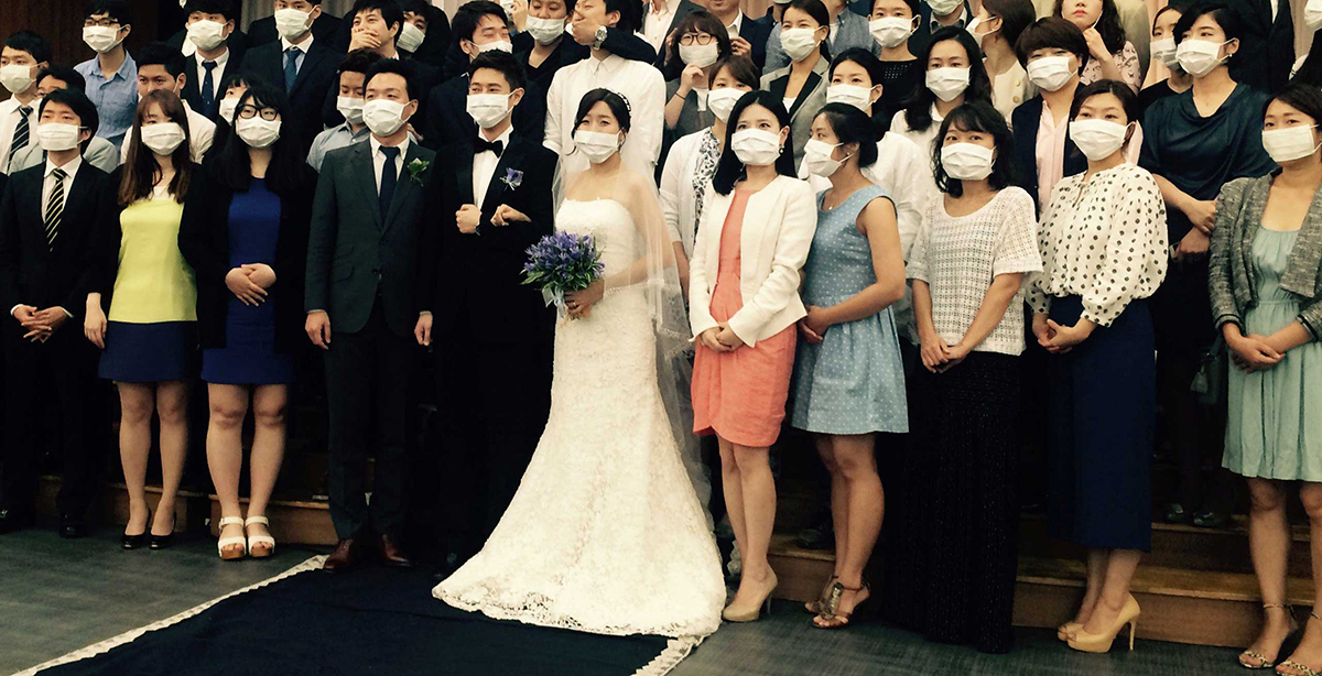 "TOPSHOTS This handout photo taken on June 6, 2015 in Seoul and released by wedding planner 'Sewing for the Soil' shows a young South Korean couple (C) and dozens of guests standing together for a group photo -- almost all of their faces shielded by white masks. The young South Korean couple became an unexpected symbol of the MERS health scare sweeping the nation after a different photo of the same group showing the couple and guests jokingly posed wearing surgical masks went viral. AFP PHOTO / Sewing for the Soil ----- EDITORS NOTE ----- RESTRICTED TO EDITORIAL USE MANDATORY CREDIT ""AFP PHOTO / Sewing For The Soil"" NO MARKETING - NO ADVERTISING CAMPAIGNS - DISTRIBUTED AS A SERVICE TO CLIENTS - NO ARCHIVESSewing For The Soil/AFP/Getty Images"