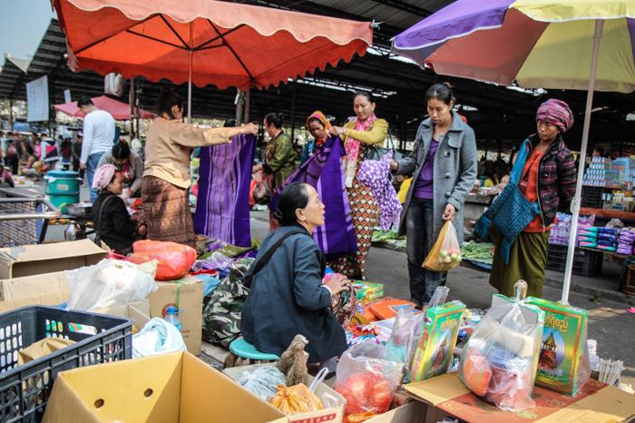 Des femmes, Shan et chinoises, regardent les tissus au marché de Mong LaCrédits : Adam Ramsey