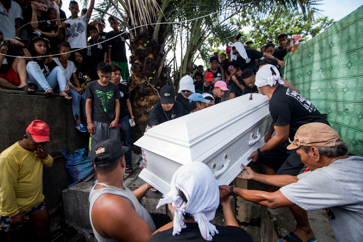 "Family and friends slain rickshaw driver Eric Sison help carry his remains to its final resting place, August 31, at the Pasay Municipal Cemetery in Pasay City, Philippines. Sison was killed as he was surrendering, on August 23, in a ""routine anti-criminality patrol"" by Pasay Police."