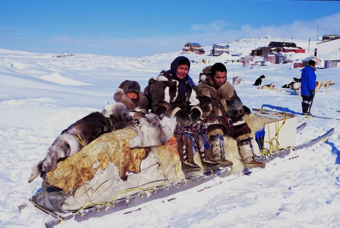 Des jeunes inuits assis sur un traîneau, à Cape DorsetCrédits