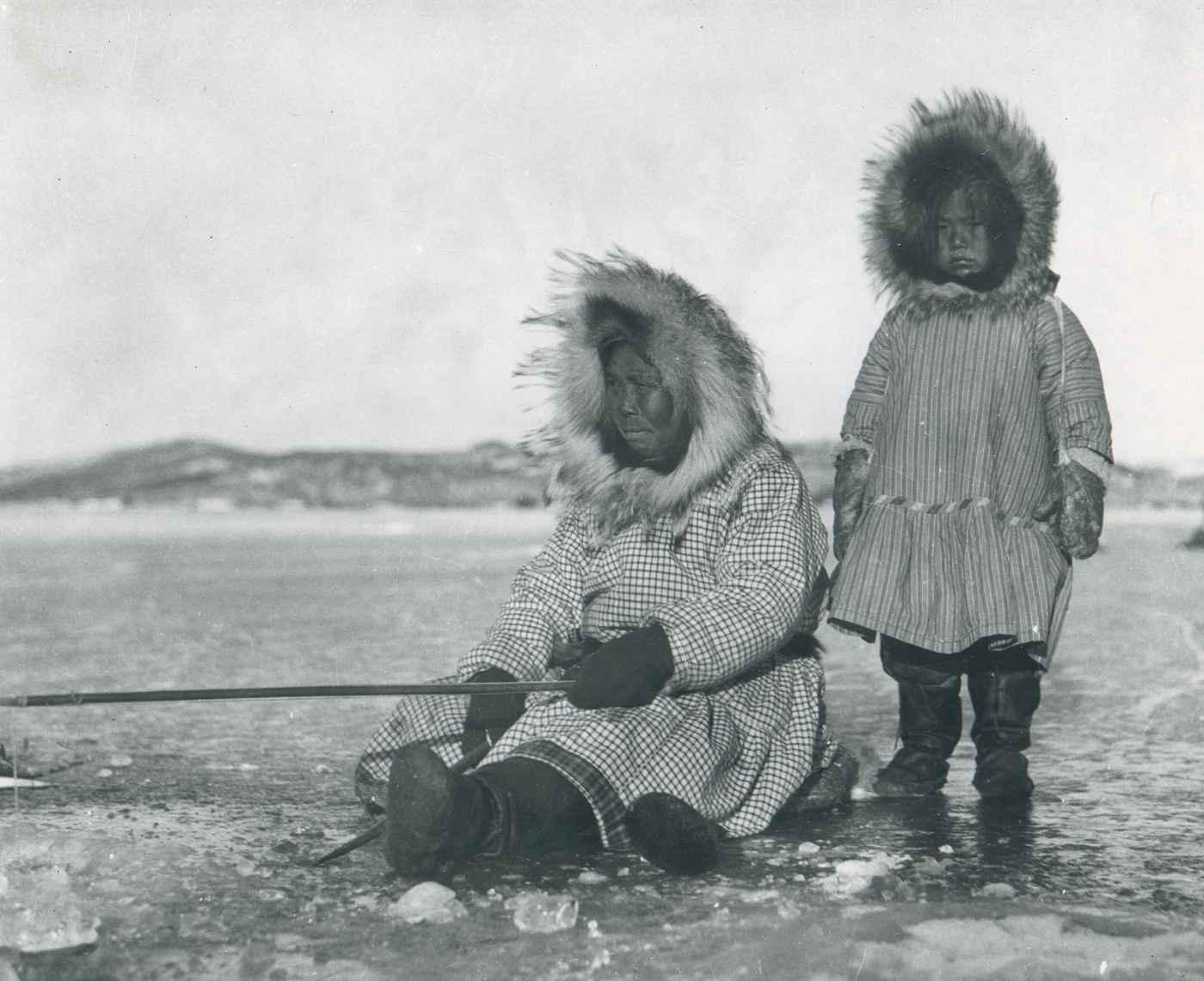 Une femme inuit pêche avec une petite filleCrédits