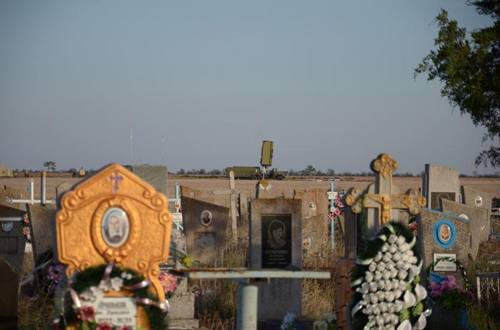 Un cimetière, avec un véhicule de l'armée ukrainienne en arrière planDimiter Kenarov